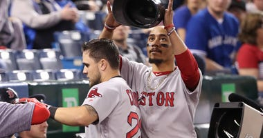 Mookie Betts removes Michael Chavis' helmet after the rookie scored