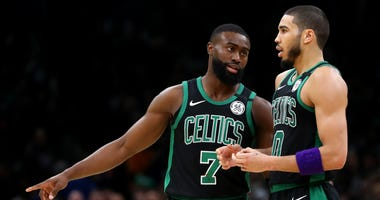 Jaylen Brown talks with Jayson Tatum during the Celtics' game against the Rockets in Boston