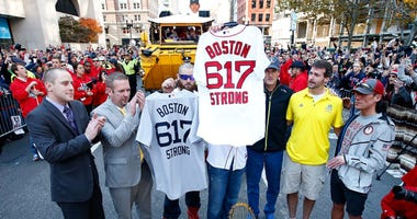 Jarrod Saltalamacchia raises a Boston Strong jersey at the Marathon finish line.