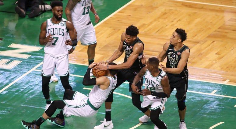 Jayson Tatum battles Giannis Antetokounmpo for the ball