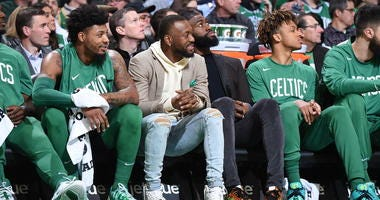 Marcus Smart, Kemba Walker and Jaylen Brown watch their teammates take on the Suns