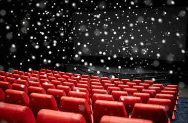 Entertainment and leisure concept - movie theater or cinema empty auditorium with red seats over snowflakes