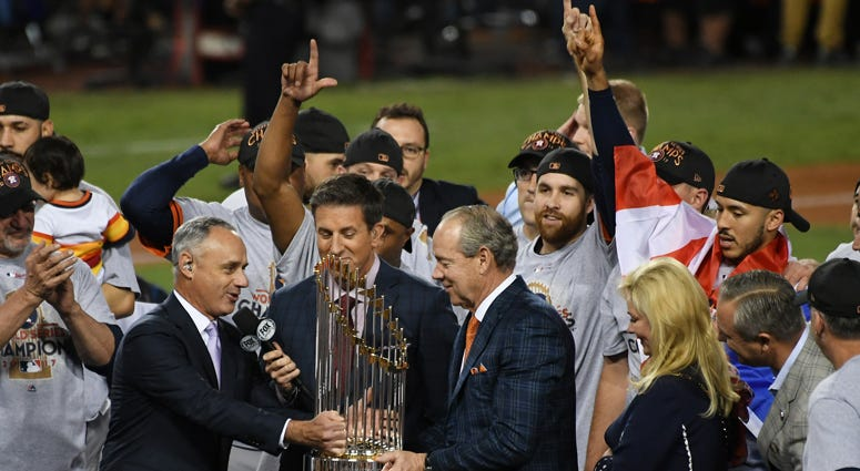 MLB commissioner Rob Manfred presents Astros owner Jim Crane with the Commissioner's Trophy after the Astros defeated the Dodgers in Game 7 to win the World Series on Nov. 1, 2017, at Dodger Stadium in Los Angeles.