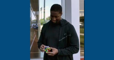 In this image taken from video, New York Jets rookie offensive lineman Calvin Anderson works on a Rubik's Cube at the NFL football team's practice facility in Florham Park, N.J.