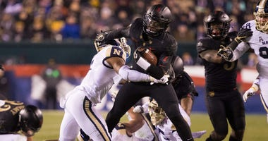 Army quarterback Kelvin Hopkins Jr. runs for a first down past the tackle attempt of Navy Midshipmen defensive back Michael McMorris on Dec. 8, 2018, at Lincoln Financial Field in Philadelphia.