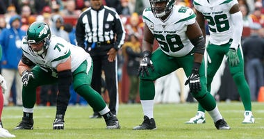 New York Jets offensive guard Alex Lewis (71), Jets offensive tackle Kelvin Beachum (68), and Jets running back Le'Veon Bell (26) line up against the Washington Redskins at FedExField
