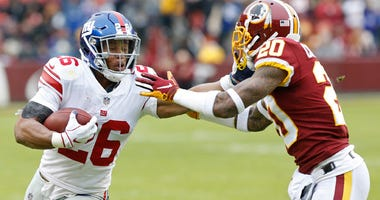 Giants running back Saquon Barkley carries the ball as Washington Redskins strong safety Ha Ha Clinton-Dix chases in on Dec. 22, 2019, at FedEx Field in Landover, Maryland.