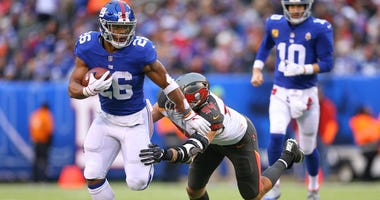 Nov 18, 2018; East Rutherford, NJ, USA; New York Giants running back Saquon Barkley (26) rushes past Tampa Bay Buccaneers cornerback Brent Grimes. Vincent Carchietta-USA TODAY Sports