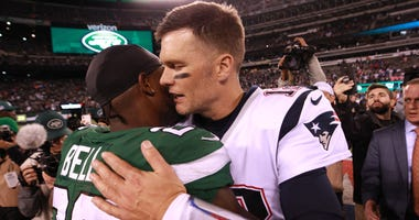 New England Patriots quarterback Tom Brady (12) hugs New York Jets running back Le'Veon Bell (26) after a game at MetLife Stadium