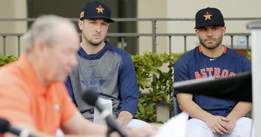 Alex Bregman and Jose Altuve of the Houston Astros look on as owner Jim Crane reads a prepared statement during a press conference at FITTEAM Ballpark of The Palm Beaches on February 13, 2020 in West Palm Beach, Florida.