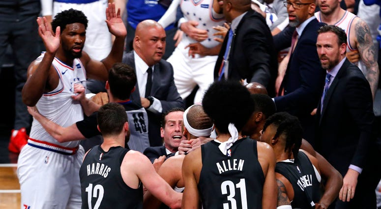 Nets coach Kenny Atkinson stops forward Jared Dudley from going after 76ers center Joel Embiid during the second half of a playoff game on April 20, 2019, at Barclays Center.