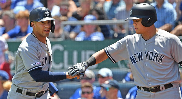 Yankees shortstop Gleyber Torres celebrates with teammate Gio Urshela after scoring a run on May 26, 2019, against the Royals in Kansas City, Missouri.
