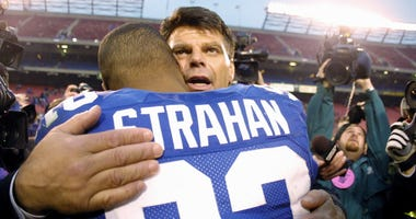 Mark Gastineau hugs Michael Strahan #92 of the New York Giants after Strahan broke his single sack record during the game against the Green Bay Packers at Giants Stadium in East Rutherford, New Jersey.
