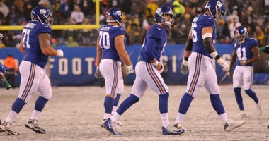 The Giants walk off the field against the Packers.