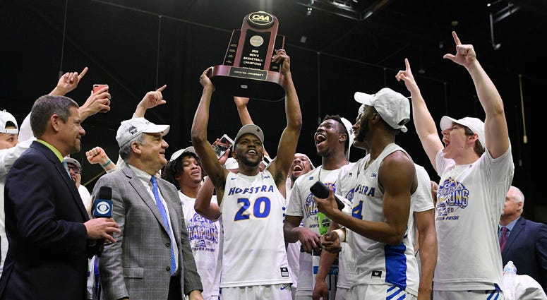 Hofstra guard Jalen Ray (20) and others raise the trophy after defeating Northeastern in an NCAA college basketball game for the championship of the Colonial Athletic Association men's tournament Tuesday, March 10, 2020, in Washington. Hofstra won 70-61.