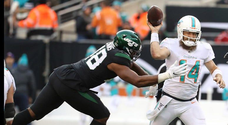 Dolphins quarterback Ryan Fitzpatrick passes as he is pressured by Jets linebacker Jordan Jenkins on Dec. 8, 2019, at MetLife Stadium.