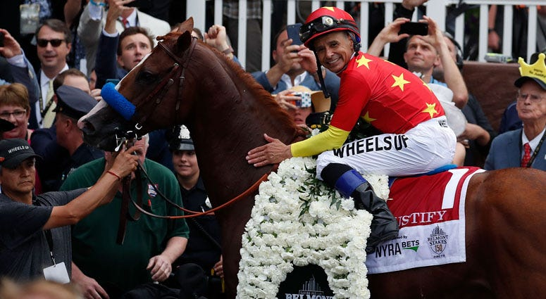 Mike Smith aboard Justify poses for photos in the winner circle after winning the 150th Belmont Stakes and Triple Crown at Belmont Park on June 9, 2018.