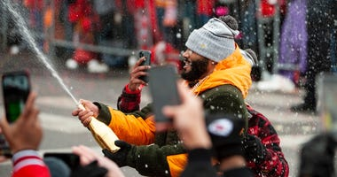 Kansas City Chiefs safety Jordan Lucas (24) sprays fans with champagne during the Super Bowl LIV championship parade through downtown Kansas City