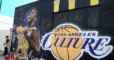 Fans gather at a mural painted in an alley on Lebanon Street in Los Angeles that pays tribute to Kobe Bryant who was killed in a helicopter crash Jan 26, 2020.