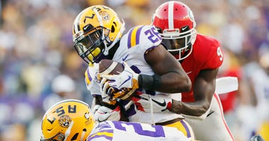 LSU safety John Battle (26), with assistance from cornerback Greedy Williams (29), intercepts a pass from Georgia quarterback Jake Fromm intended for wide receiver Jeremiah Holloman, rear, during the fourth quarter of an NCAA college football game Saturda