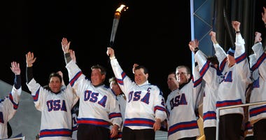 Mike Eruzione and other members of the 1980 gold medal-winning USA men's hockey team hold up the torch before lighting the Olympic flame at the Opening Ceremony of the Salt Lake City Winter Olympic Games at the Rice-Eccles Olympic Stadium