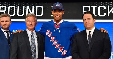 K'Andre Miller poses for a photo with team representatives after being selected as the number twenty-two overall pick to the New York Rangers in the first round of the 2018 NHL Draft at American Airlines Center.