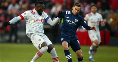 Jozy Altidore of Toronto FC dribbles the ball as James Sands of New York City FC defends during the first half of an MLS game at BMO Field on March 07, 2020 in Toronto, Canada.