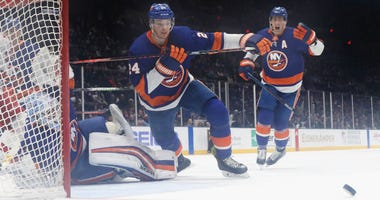 Thomas Greiss, Scott Mayfield and Brock Nelson of the Islanders defend against the Carolina Hurricanes at NYCB Live's Nassau Coliseum on March 07, 2020 in Uniondale, New York.