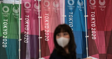 A woman walks past Tokyo 2020 Olympics banners on March 19, 2020 in Tokyo.