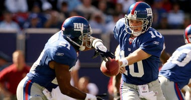Eli Manning #10 of the New York Giants hands the ball off to Tiki Barber #21 against the Washington Redskins on October 8, 2006 at Giants Stadium in East Rutherford, New Jersey