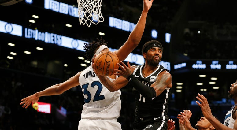 Nets guard Kyrie Irving attempts a pass against Timberwolves center Karl-Anthony Towns Oct 23, 2019; Brooklyn, NY
