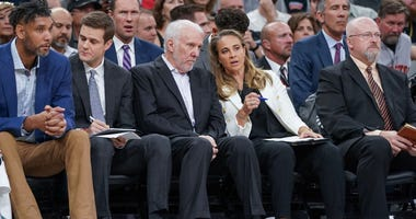 San Antonio Spurs head coach Gregg Popovich and assistant head coach Becky Hammon speak on the Spurs bench Oct 23, 2019; San Antonio, TX