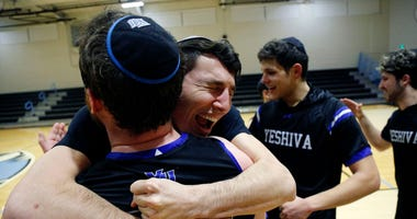 Yeshiva forward Michael Bixon hugs forward Daniel Katz, back to camera, after the team's 102-83 win over Penn State-Harrisburg in the second round of the NCAA men's Division III college basketball tournament on March 7, 2020, in Baltimore.