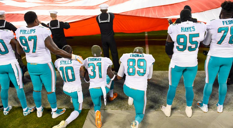 Miami Dolphins players kneel during the national anthem on Nov. 13, 2018, at Bank of America Stadium in Charlotte, North Carolina.