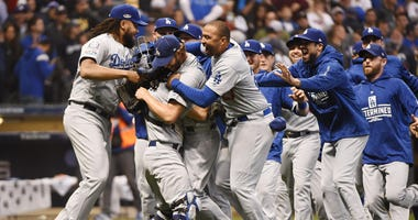 Dodgers pitcher Clayton Kershaw (22) celebrates with teammates after defeating the Milwaukee Brewers in Game 7 of the NLCS at Miller Park in Milwaukee.
