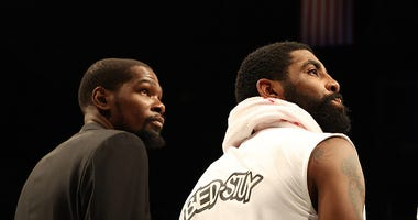 Kevin Durant and Kyrie Irving look on from the bench during a Nets game.