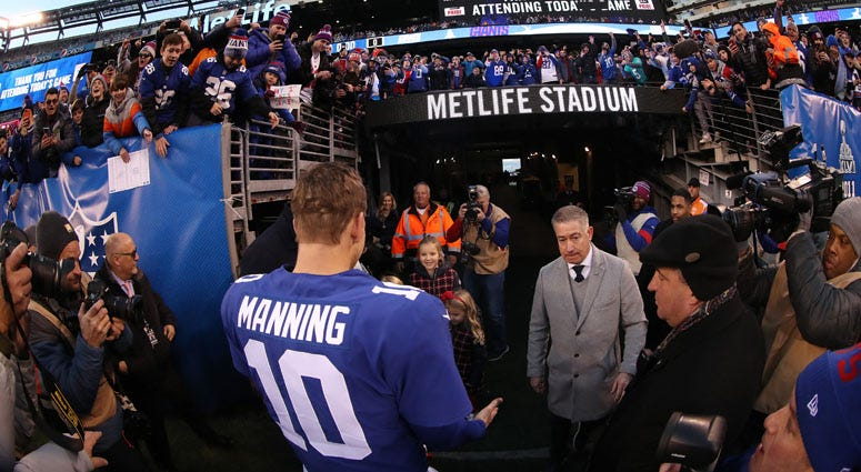 Eli Manning meets his family after the Giants' 36-20 win against the Miami Dolphins on Dec. 15, 2019, at MetLife Stadium.