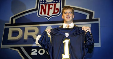 Eli Manning holds up a San Diego Chargers jersey after being selected first overall by the team in the 2004 NFL draft on April 24, 2004. Shortly after, he was traded to the New York Giants. (Photo by Chris Trotman/Getty Images)