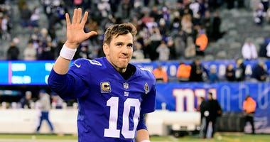 Eli Manning waves while jogging off the field at MetLife Stadium