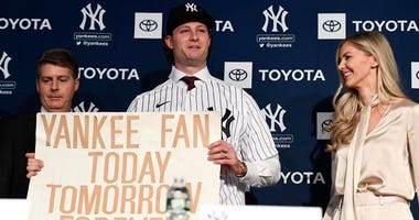 Yankees pitcher Gerrit Cole holds the sign he was photographed with at the 2001 World Series as a kid. Danielle Parhizkaran/USA TODAY Images