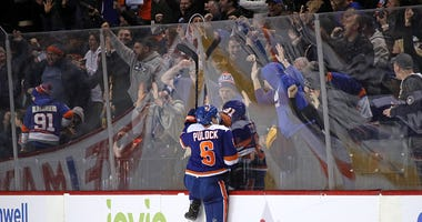 Ryan Pulock celebrates a goal for the Islanders with fans.