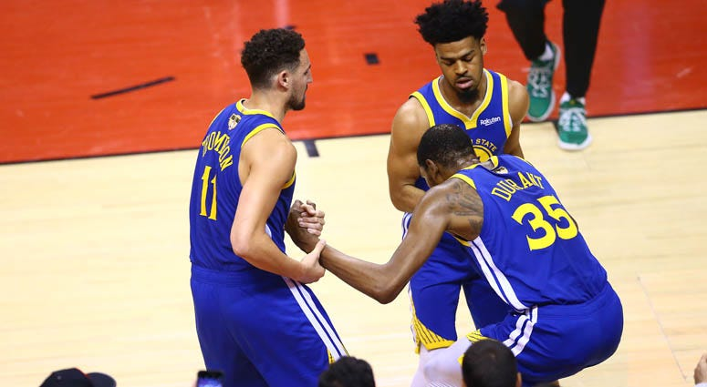 Kevin Durant (35) is helped to his feet by Klay Thompson (11) and Quinn Cook of the Golden State Warriors after sustaining an injury against the Raptors in Game 5 of the 2019 NBA Finals on June 10, 2019, at Scotiabank Arena in Toronto, Canada.