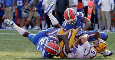 LSU quarterback Joe Burrow is tackled by Florida defensive back Chauncey Gardner-Johnson (23) and defensive back CJ Henderson on Oct. 6, 2018, in Gainesville, Florida.