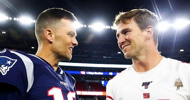 Tom Brady and Eli Manning shake hands.