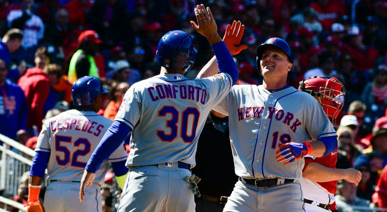 Mets right fielder Jay Bruce (19) high-fives Michael Conforto after hitting a grand slam against the Washington Nationals on April 5, 2018, at Nationals Park in Washington, D.C.