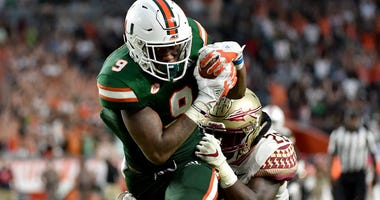 Miami Hurricanes tight end Brevin Jordan (9) runs in a touchdown as Florida State Seminoles linebacker DeCalon Brooks (28) defends the play during the second half at Hard Rock Stadium.