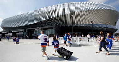 In this Sept. 17, 2017, file photo, hockey fans make their way toward the entrances of the renovated Nassau Veterans Memorial Coliseum in Uniondale, N.Y., before a preseason game against the Philadelphia Flyers.