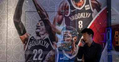 A Chinese man talks on his phone next to a billboard showing players from the Brooklyn Nets outside the NBA flagship retail store on Oct. 9, 2019 in Beijing.
