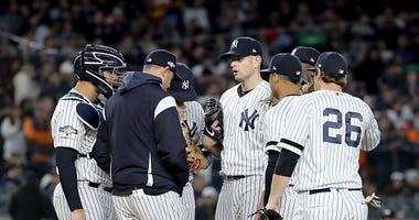 Aaron Boone talks with James Paxton on the mound during the ALCS.