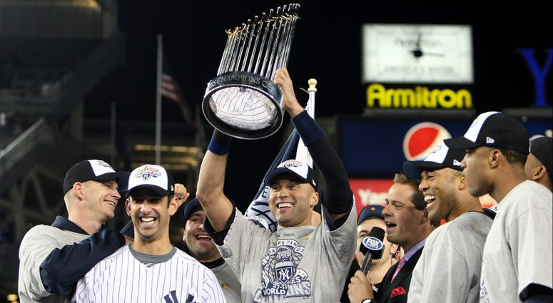 Derek Jeter #2 of the New York Yankees holds up the trophy as he celebrates Game Six of the 2009 MLB World Series at Yankee Stadium